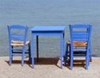 Havsblåa stolar och bord på en strand i Grekland