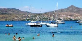Stranden i Agia Marina med blåa havet, badande gäster och segelbåtar