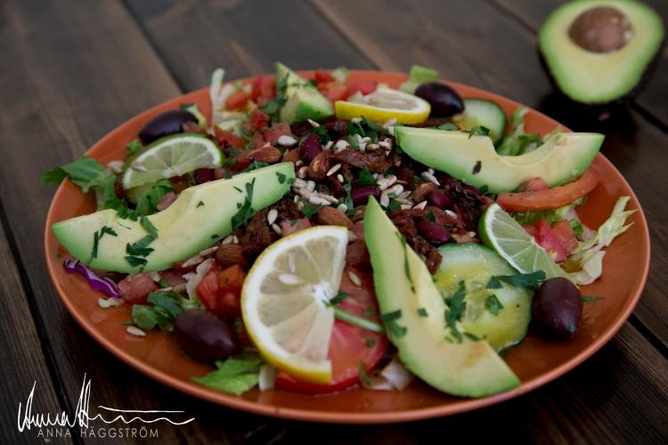 Vegansk salladmedhackade tomater med vitlök, rostade mandlar, solrosfrön, röda bönor, avokado, kalamataoliver, soltorkade tomater, röd lök, ruccola, limeklyftor, blandad sallad, persilja.